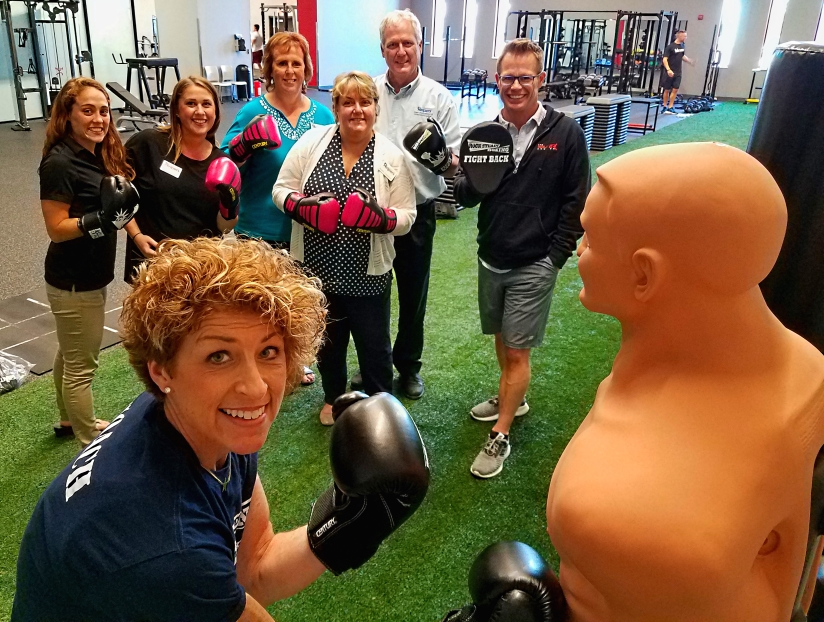 Foreground is Cindy Murphy, Certified Personal Trainer at The Miller Center, and Rock Steady Boxing instructor. Background, from left to right, Robin Barth, Director of Fitness Operations for The Miller Center, Courtney Matrey, Community Care Coordinator for Senior Helpers, Brenda Buckles, Client Service Manager for Senior Helpers, Bobbi and John Emanuel, Owners of Senior Helpers (Sunbury location), and Matt Miller, Founder of The Miller Center for Recreation and Wellness.